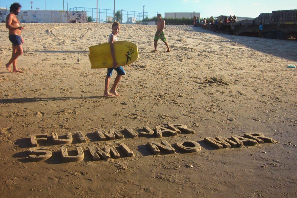 FUI MIJAR SUMI NO MAR - BLOCK LETTER. Texto moldado na areia da praia.